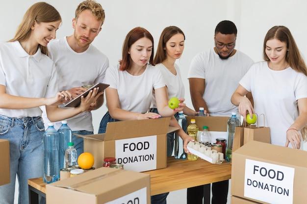 Muitos voluntários preparando caixas com doações de alimentos