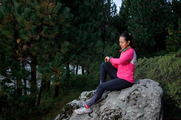 Mujer corredora usando seu reloj inteligente depois de correr sentada no orilla del lago