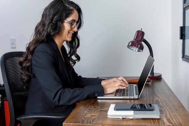 Mujer ejecutiva latina trabalhando em seu ordenador porttil desde casa debido a la cuarentena
