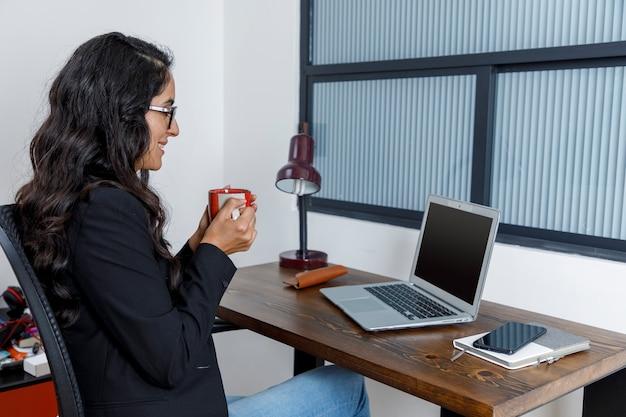 Mujer ejecutiva tomando uma taza de cafe mientras esta en conferencia en seu ordenador portatil