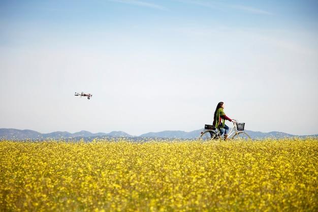 Mujer joven en bici por campo mientras un drone vuela detrás de ella