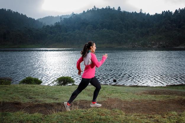 Mujer latina atleta corriendo al aire libre cerca de um lago com montanhas ao fundo