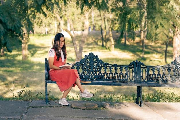 Mujer latina sentada em uma banca de um parque lendo um livro