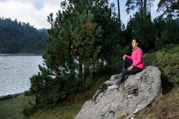 Mujer sentada em uma roca a la orilla de um lago com arboles ao fundo