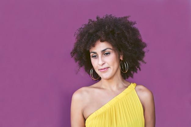 Mulata de cabelos negros em um vestido amarelo e fundo roxo.