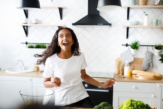 Mulata engraçada, movendo-se com a boca cheia de comida na cozinha moderna, vestida com camiseta branca