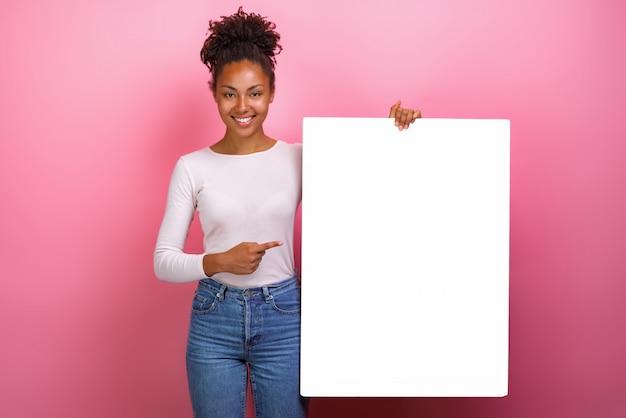 Mulata feliz apontando para copyspace de folha de papel branco vazio