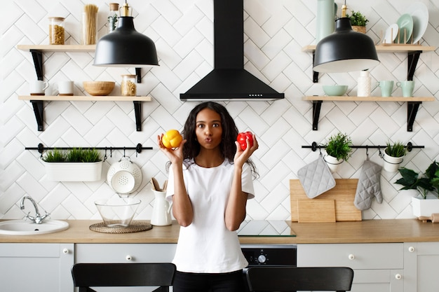 Mulata vestida com camiseta branca, com cara engraçada e cabelo solto está segurando pimentões vermelhos e amarelos nas mãos perto das bochechas na cozinha moderna