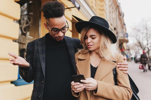 Mulato encaracolado surpreso abraçando a mulher loira magnífica. mulher loira atraente andando na rua e conversando com o amigo africano do sexo masculino.