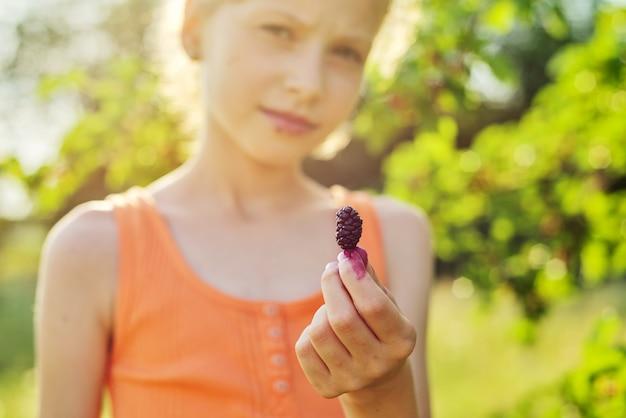 Mulberrie berrie madura na mão de uma menina, uma criança na natureza perto de uma árvore com amoreira