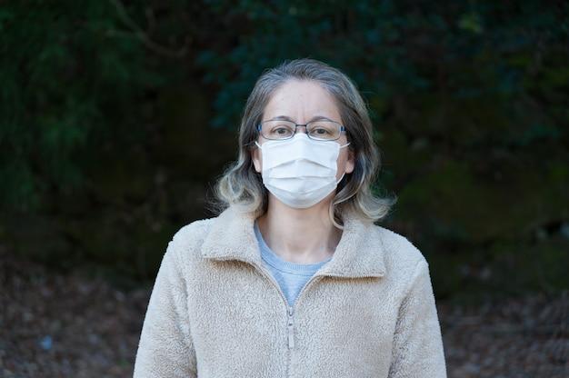 Mulher 4049 anos usando óculos e máscara branca para proteção contra covid19