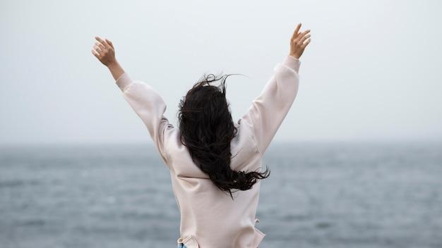 Mulher à beira-mar com os braços levantados