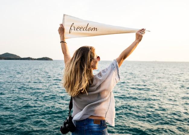 Mulher à beira-mar segurando uma bandeira com a inscrição da liberdade