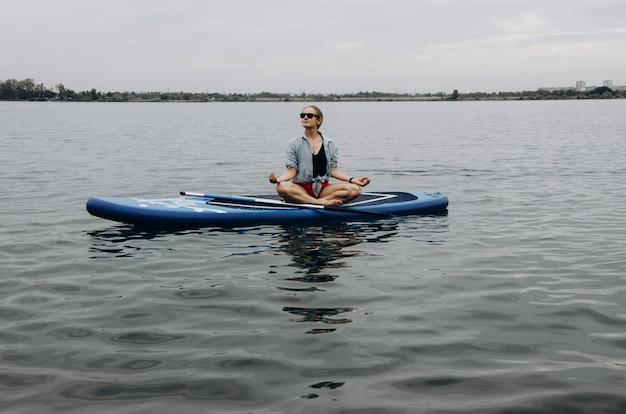 Mulher a bordo do sup. uma bela jovem relaxa em uma placa de sup. stand up paddle