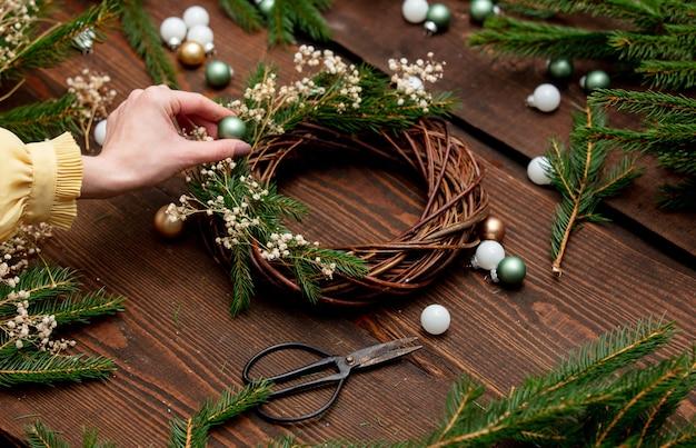 Mulher a decorar uma coroa de flores para o natal