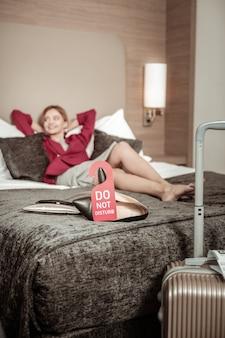 Mulher a descansar. mulher de negócios loira descansando deitada na cama em um quarto de hotel depois do aeroporto