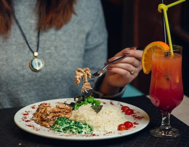 Mulher a jantar com arroz, ervas e um copo de suco de laranja vermelho.