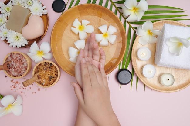 Mulher a mergulhar as mãos numa tigela de água e flores, tratamento e produto spa para pés e mãos femininas, massagem seixo, água de flores perfumadas e velas, relaxamento. postura plana. vista do topo.