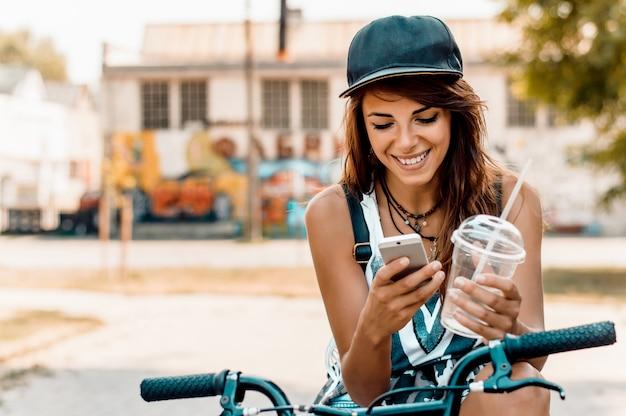 Mulher à moda nova com uma bicicleta usando o telemóvel.