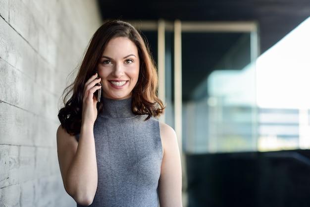 Mulher à moda que fala no móbil