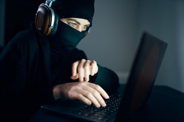 Mulher à noite em frente ao laptop usando fones de ouvido, tecnologia de internet