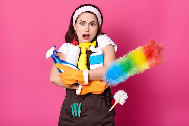 Mulher abraça muitas garrafas de detergente, espanador pp, vestida de camiseta branca, avental marrom, faixa de cabelo