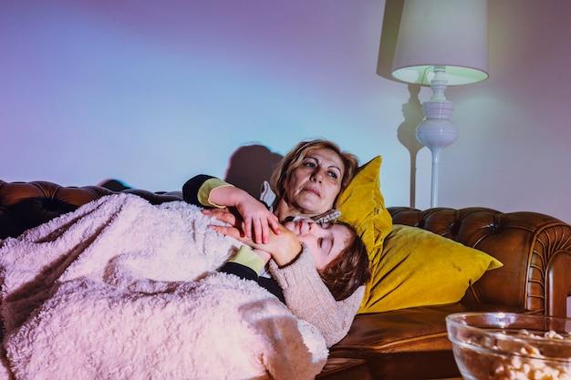 Mulher abraçada com filha no sofá