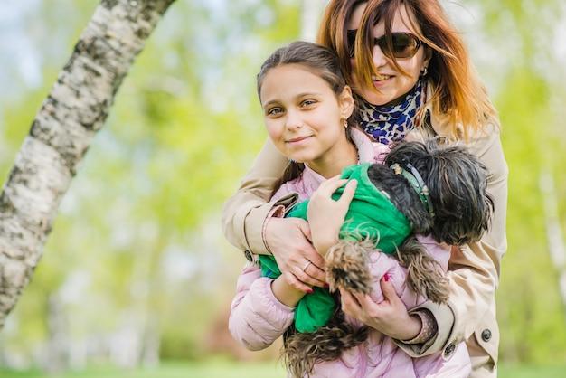 Mulher abraçando a filha e o cachorro