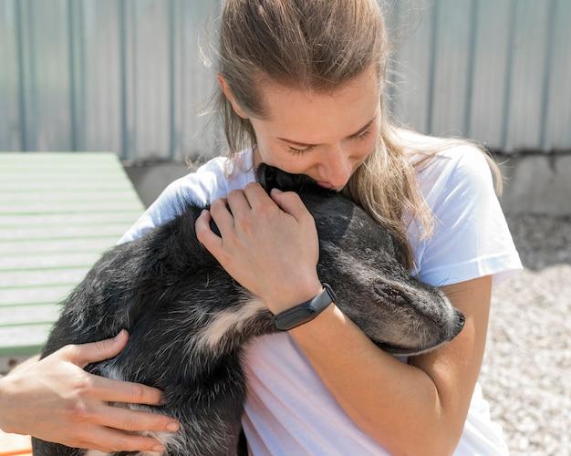 Mulher abraçando cachorro fofo de resgate