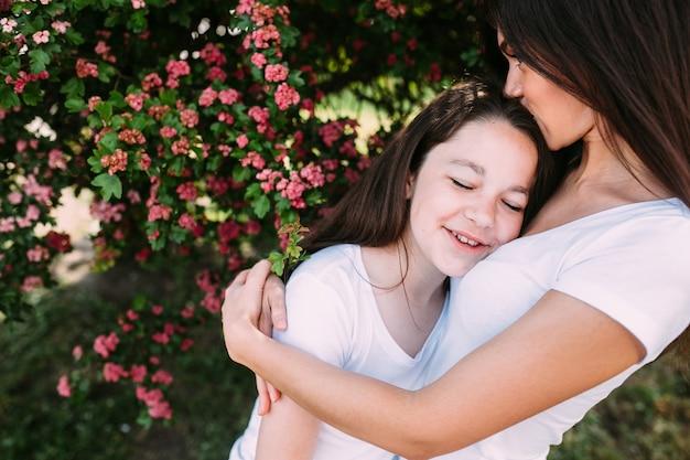 Mulher abraçando e beijando menina sob a árvore
