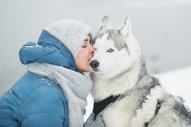Mulher abraçando e beijando o husky siberiano nevado no inverno
