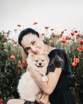 Mulher abraçando filhote de cachorro da pomerânia em um fundo de campo de flores
