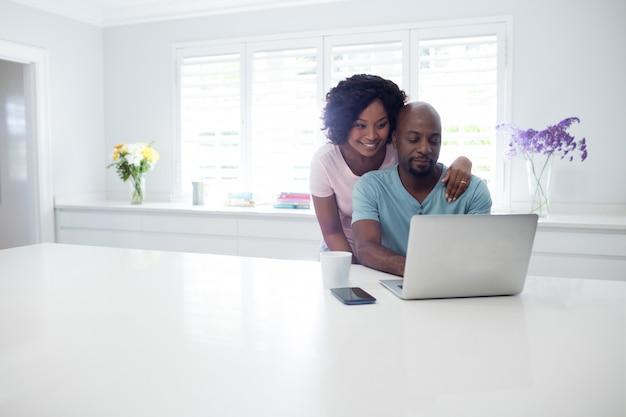 Mulher, abraçando, homem, enquanto, usando computador portátil
