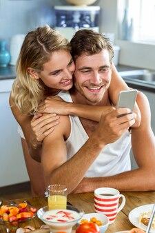 Mulher, abraçando, homem, usando telefone móvel, em casa
