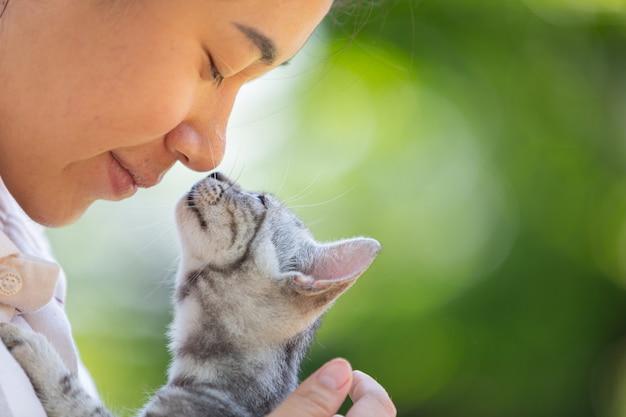 Mulher abraçando o gato no jardim