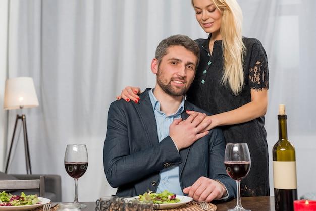 Mulher abraçando o homem na mesa com pratos e copos