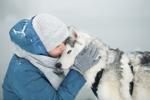 Mulher abraçando o husky siberiano nevado no inverno