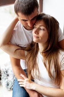 Mulher abraçando o marido e olhando para longe
