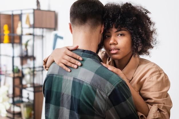 Mulher abraçando o namorado e olhando para o fotógrafo