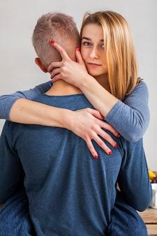 Mulher abraçando o namorado na cozinha