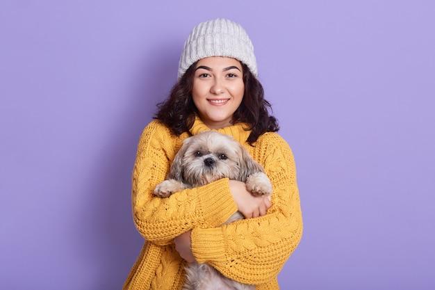 Mulher abraçando seu cachorrinho e olhando diretamente para a câmera com uma expressão facial satisfeita