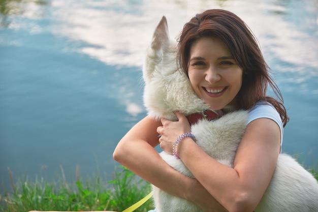 Mulher abraçando seu cachorro, tocando seu pêlo macio com as mãos e o rosto com água refletindo