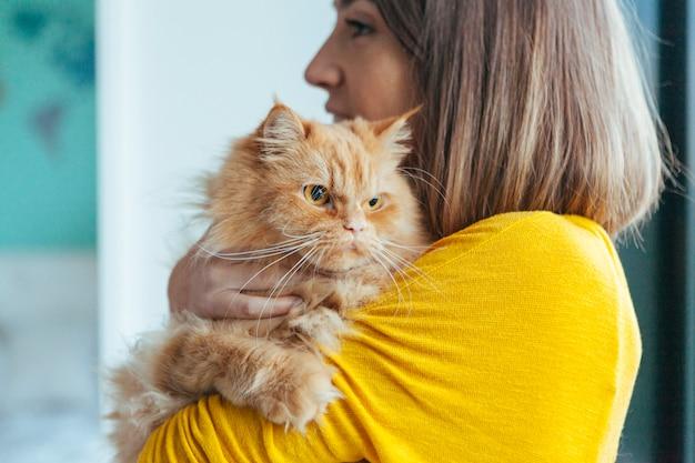 Mulher abraçando seu gato