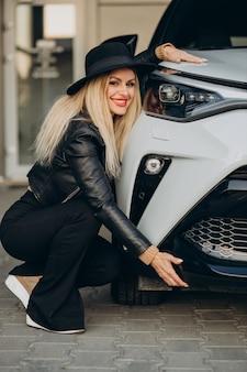 Mulher abraçando um carro branco novo