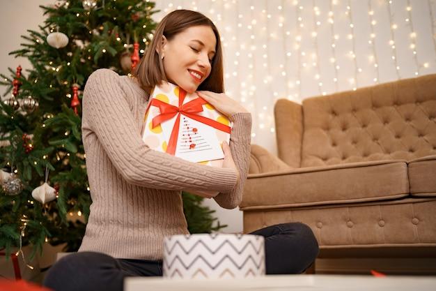 Mulher abraçando uma caixa de presente enquanto está sentada entre muitos presentes na sala de estar decorada de natal
