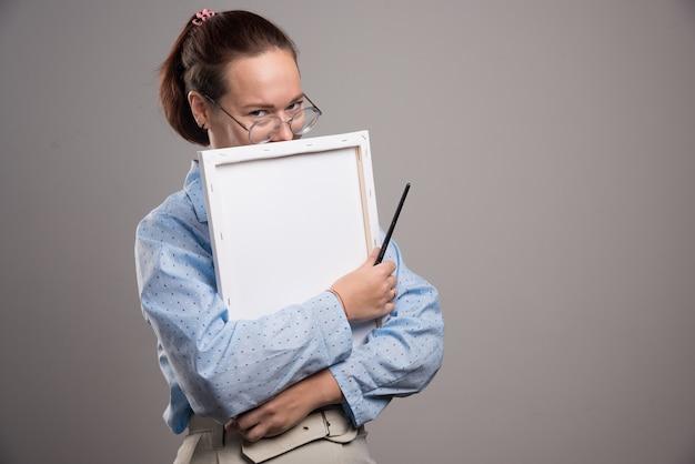 Mulher abraçando uma tela vazia com um pincel no fundo cinza