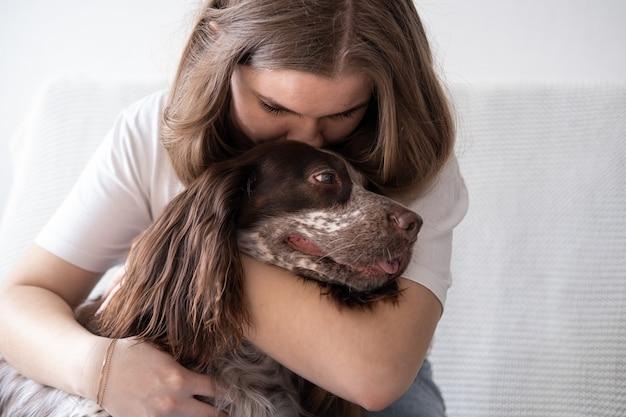 Mulher abraço olhos de cores diferentes de cão spaniel russo chocolate merle. conceito de cuidados de animais de estimação.