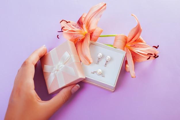Mulher abre a caixa de presente com conjunto de joias com pérolas e flores. brincos e anel com lírio.