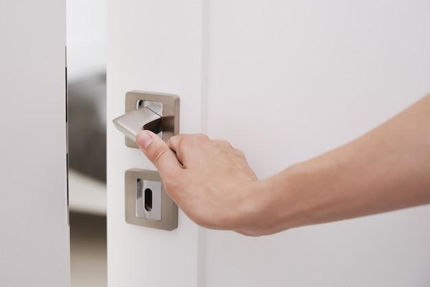 Mulher abre a porta branca com uma maçaneta e entra na sala