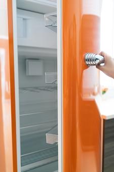 Mulher abre a porta da geladeira na cozinha